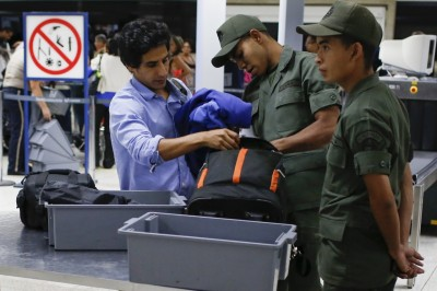Soldiers checks the luggage of a passenger in a security checkpoint at the Simon Bolivar airport in La Guaira outside Caracas