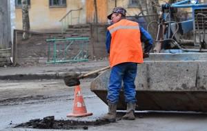 Рабочий ремонтирует дорогу