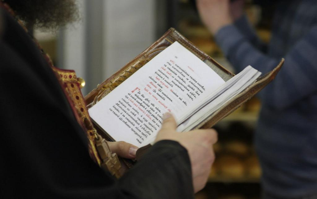 Священнослужитель читает религиозную книгу