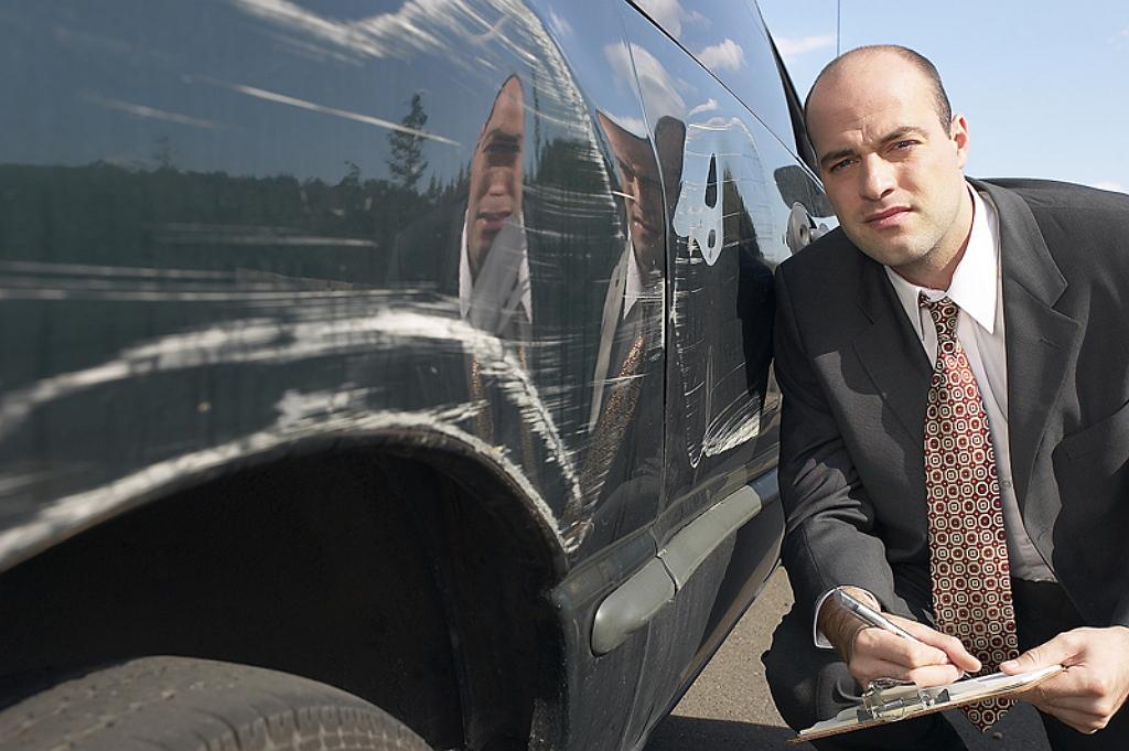 Человек в костюме оценивает ущерб причиненный автомобилю