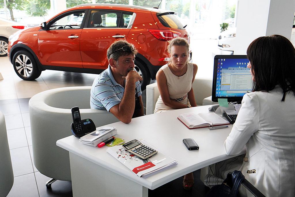 Люди беседуют с сотрудницей автосалона
