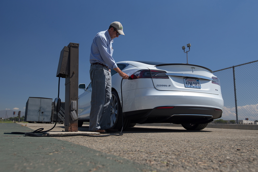 Мужчина заряжает Tesla Model S