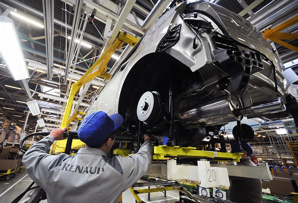 Рабочий собирает машину на заводе Renault