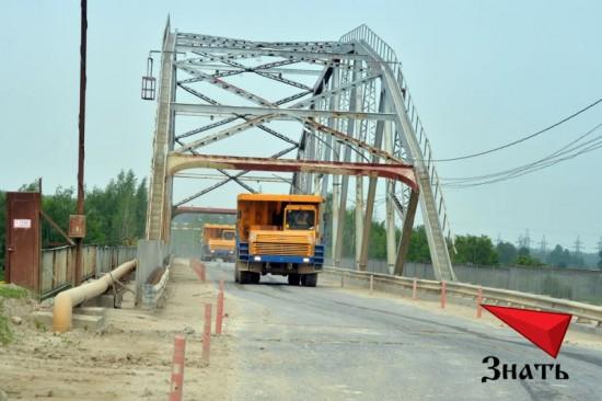 Карьерные самосвалы марки БелАз возят известняк по Афанасьевскому мосту из карьера на завод.