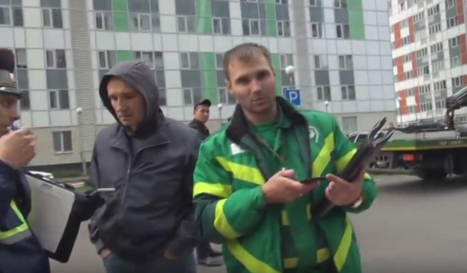 Эвакуаторщики увозят машины с парковки многоквартирного дома