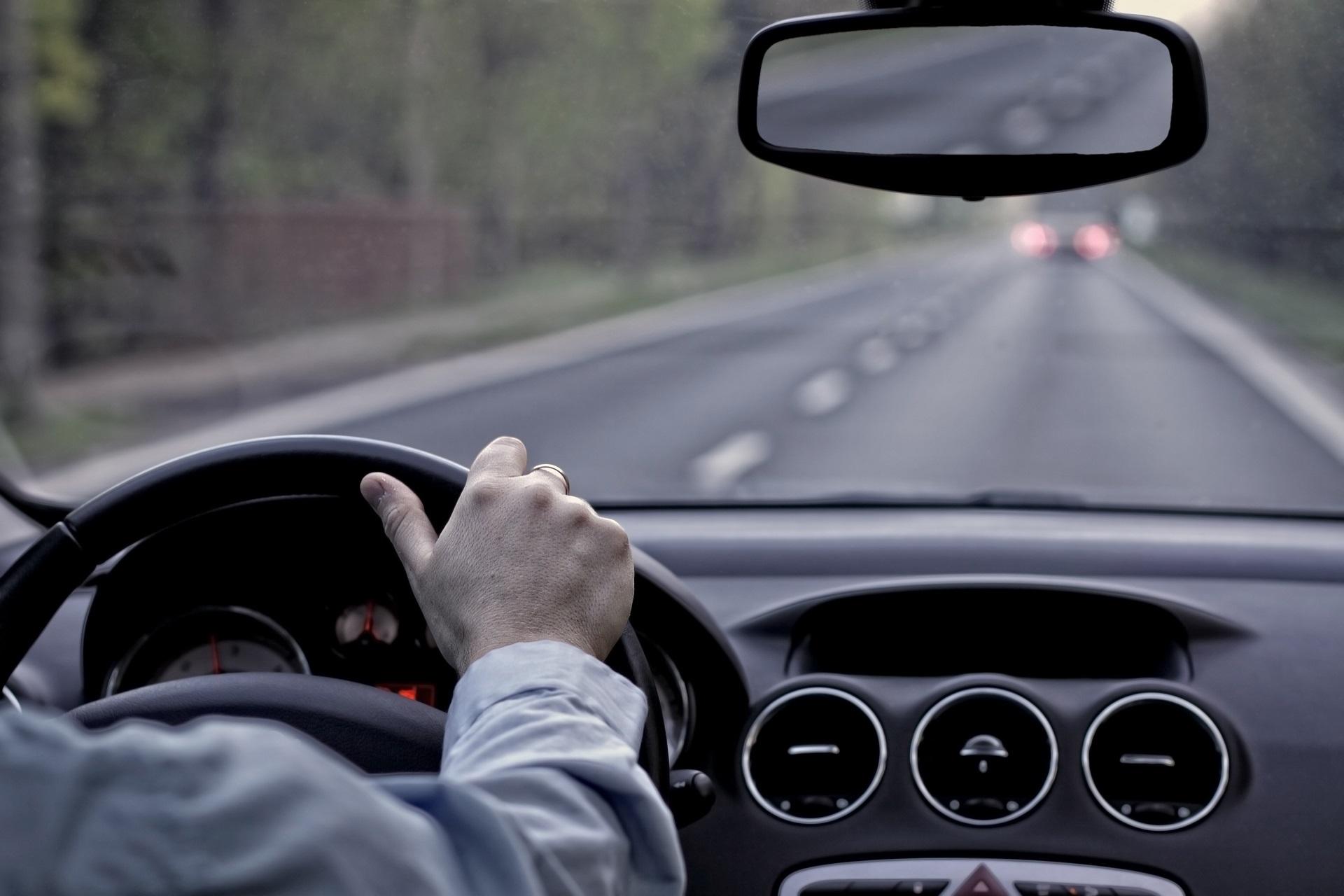 Водитель в автомобиле на дороге руль рулит