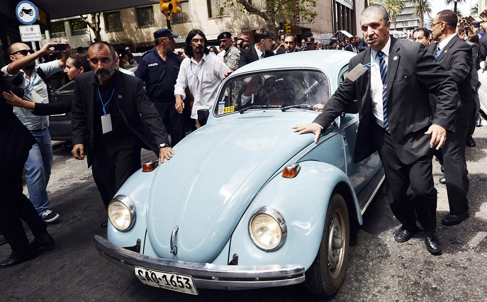 Security personnel surround the Volkswagen Beetle belonging to Jose Mujica as he is being driven away after handing over the presidential sash to Tabare Vazquez in Montevideo
