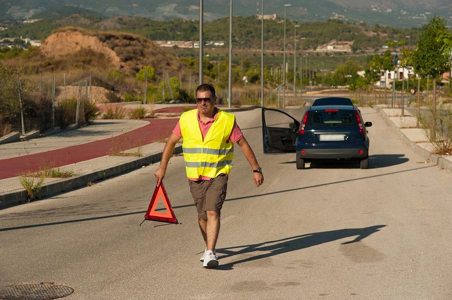 Водитель в светоотражающем жилете несет знак аварийной остановки